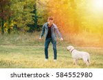 Man playing with his dog Labrador in park at sunset - stock photo