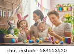 Stock photo mother father and daughters are painting eggs happy family are preparing for easter cute little 584553520