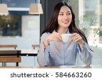 beautiful woman drinks coffee... | Shutterstock . vector #584663260