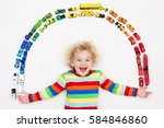 funny curly toddler boy playing ... | Shutterstock . vector #584846860