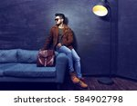 handsome young man sitting on... | Shutterstock . vector #584902798