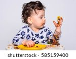 one year old kid eating a slice ... | Shutterstock . vector #585159400