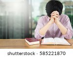 man praying on holy bible in... | Shutterstock . vector #585221870