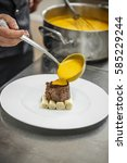 Small photo of Chef pouring gamy sauce on the food, preparing his plate for lunch