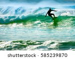 silhouette of a surfer riding a ... | Shutterstock . vector #585239870