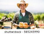 Small photo of Portrait of a smiling farmer holding box of fruit at local market