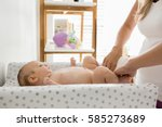 mother changing the diaper of... | Shutterstock . vector #585273689