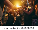 Small photo of Low angle shot of group of friends enjoying drinks at bar together. Young people at nightclub toasting cocktails.