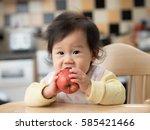 cute baby girl eating apple on... | Shutterstock . vector #585421466