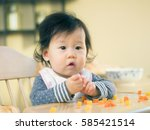 baby eating vegetable first time | Shutterstock . vector #585421514