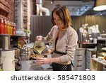Small photo of small business, people and service concept - happy woman or barmaid pouring smoothie from blender to cup at vegan cafe