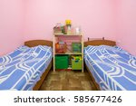 Stock photo the interior of a small dorm room with two beds and a homemade rack in the middle 585677426