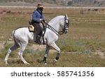 LOS ALBUREJOS, MEDINA SIDONIA, SPAIN – JULY 2009: A rider on a pure bred Spanish horse riding the vaquero style in a Spanish saddle. - stock photo