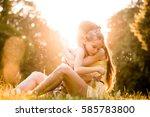 mother is cuddling her worried... | Shutterstock . vector #585783800