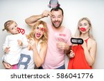 Stock photo young family at white background photo booth with party props happy funny smile strike pose 586041776