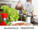 woman puts vegetables into the... | Shutterstock . vector #586059590