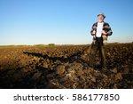 an elderly farmer standing in a ...