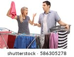 Small photo of Young couple having an argument while hanging clothes on a clothing rack dryer isolated on white background