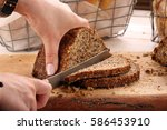 woman cut whole grain bread on... | Shutterstock . vector #586453910