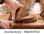 woman cut whole grain bread on... | Shutterstock . vector #586453910
