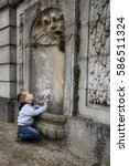 Small photo of Small boy kneeling by the fountain spouter in the historic house wall