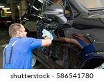 man on a car wash polishing car ... | Shutterstock . vector #586541780