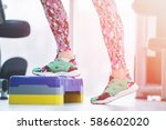 Small photo of Athletic woman trainer doing aerobic class with steppers to people group on a modern fitness center. Sport and health concept.