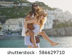 Small photo of Piggyback happy tourist friends having fun on summer travel adventure vacation laughing