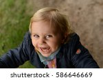 Small photo of Close up of excited, funny little blond girl looking directly at the camera. Running feisty toddler shot, natural background. Hypnotizing eyes and smile. Happy-go-lucky child being outdoors.