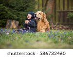 Stock photo blond big dog and baby boy in spring having fun 586732460