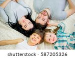 family posing on the bed in the ... | Shutterstock . vector #587205326