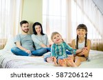 family posing on the bed in the ... | Shutterstock . vector #587206124