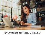 asian woman drinking coffee in... | Shutterstock . vector #587245160