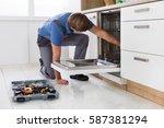 repairman examining dishwasher...   Shutterstock . vector #587381294