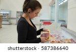 woman buys meat in supermarket... | Shutterstock . vector #587386640