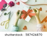 hands tie ribbon on gift box | Shutterstock . vector #587426870