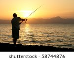 Man fishing in last rays of sunlight on sea shore - stock photo