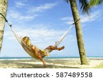 woman relaxing at the beach on... | Shutterstock . vector #587489558