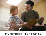 father reading a story to his... | Shutterstock . vector #587532458