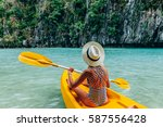 woman paddling a kayak in the... | Shutterstock . vector #587556428