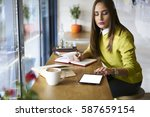 Small photo of Young attractive female administrative manager working with financial documentation and financial reports in online database checking accountings via touchpad with mock up screen connected to wifi
