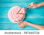Stock photo woman s hands cut the cake with pink cream on blue wood background pink cake top view 587660726