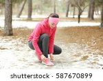 young woman tying shoelaces in... | Shutterstock . vector #587670899