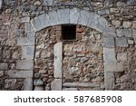 Small photo of Medieval stone wall with inbuild arch and small window