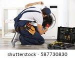 plumber repairing washing...   Shutterstock . vector #587730830