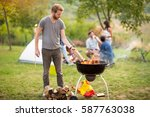 young man put log in grill fire ... | Shutterstock . vector #587763038