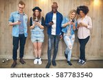 Small photo of Group of young people at party or meeting wearing casual clothes standing near wooden wall all staring at their smartphones, all smiling