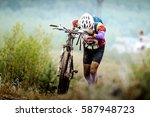 athlete cyclist mountainbiker going uphill with my bike - stock photo