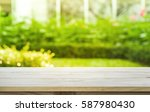 empty wood table top on lawn... | Shutterstock . vector #587980430