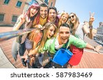 Stock photo group of multicultural tourists friends having fun taking selfie and shouting out at old town tour 587983469